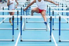 Dos altas colegialas que compiten con en los 100 obstáculos del metro Fotografía de archivo