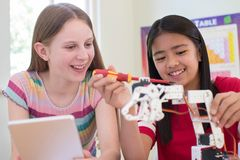 Dos alumnos femeninos en la lección de la ciencia que estudian la robótica fotos de archivo