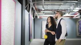 Dos amantes del arte están hablando de la imagen abstracta en museo en la abertura metrajes