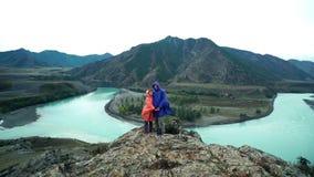 Dos amantes en impermeables divertidos se están colocando al borde de la montaña y llevan a cabo las manos Visión posterior metrajes