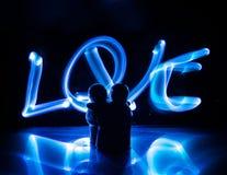 Dos amantes jovenes pintan un corazón en el fuego Silueta de pares y de palabras del amor en un fondo oscuro Foto de archivo