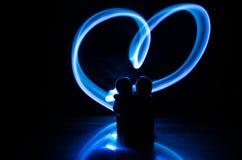 Dos amantes jovenes pintan un corazón en el fuego Silueta de pares y de palabras del amor en un fondo oscuro Imagenes de archivo
