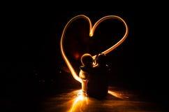 Dos amantes jovenes pintan un corazón en el fuego Silueta de pares y de palabras del amor en un fondo oscuro Imágenes de archivo libres de regalías