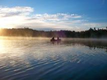 Dos amantes mandilan en su canoa en una madrugada imagenes de archivo