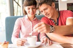 Dos amantes que charlan y que se divierten en el café Imagenes de archivo