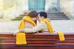 Dos amantes que se sientan en banco en parque y que se sostienen por las manos Fotos de archivo