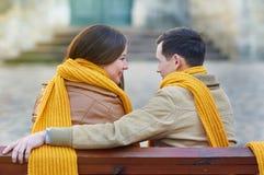 Dos amantes que se sientan en banco en parque y que se sostienen por las manos Foto de archivo