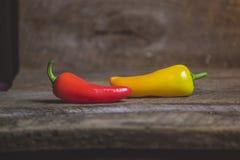 Dos amarillos y pimientas vegetales rojas en el fondo de madera Foto de archivo libre de regalías