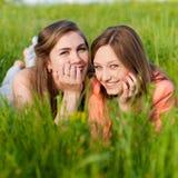 Dos amigas adolescentes que ríen en hierba verde Fotos de archivo