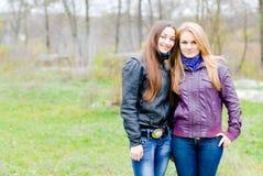 Dos amigas adolescentes que ríen en primavera u otoño al aire libre Fotos de archivo libres de regalías
