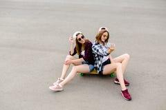 Dos amigas felices jovenes en el equipo del inconformista que se sienta junto en longboard y que hace el selfie en el teléfono fotos de archivo