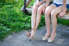 Dos amigas que se sientan en el primer de las piernas del banco de madera Imágenes de archivo libres de regalías