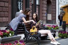 Dos amigas que se sientan en un banco en el centro de ciudad Fotos de archivo