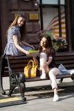 Dos amigas que se sientan en un banco en el centro de ciudad Imagenes de archivo