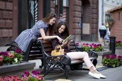 Dos amigas que se sientan en un banco en el centro de ciudad Imagen de archivo libre de regalías