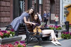 Dos amigas que se sientan en un banco en el centro de ciudad Imágenes de archivo libres de regalías
