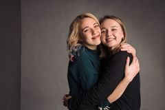 Dos amigas que se unen, abrazando, riendo y sonriendo El estudio tirado en la pared gris Imagenes de archivo
