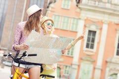 Dos amigas que usan el mapa mientras que monta la bicicleta en tándem Fotos de archivo