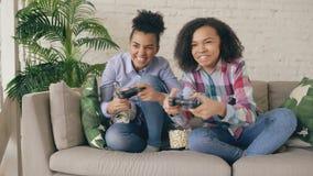 Dos amigas rizadas de la raza mixta que se sientan en juego del sofá consuelan los juegos de ordenador con el gamepad y se divier almacen de metraje de vídeo