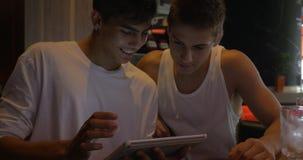 Dos amigos adolescentes con la tableta en café almacen de metraje de vídeo