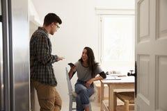 Dos amigos adolescentes que usan los smartphones, hablando en cocina Fotografía de archivo