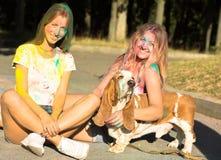 Dos amigos alegres de las mujeres jovenes que juegan con el perro grande en el FE de Holi Imágenes de archivo libres de regalías