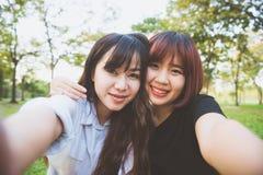 Dos amigos asiáticos jovenes felices hermosos de las mujeres que se divierten junto en el parque y que toman un selfie Imágenes de archivo libres de regalías