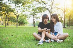 Dos amigos asiáticos jovenes felices hermosos de las mujeres que se divierten junto en el parque y que toman un selfie Imagenes de archivo
