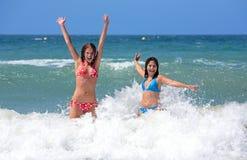 Dos amigos atractivos de la chica joven que juegan en el mar el vacaciones Foto de archivo libre de regalías