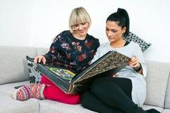 Dos amigos atractivos de la mujer con el álbum de foto Imágenes de archivo libres de regalías