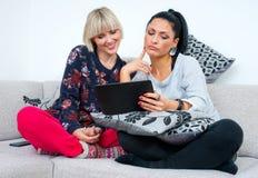 Dos amigos atractivos de la mujer con la tableta Fotos de archivo libres de regalías