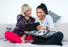Dos amigos atractivos de la mujer con la tableta Fotografía de archivo libre de regalías