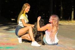 Dos amigos atractivos de las mujeres que juegan con el perro grande en el festiv de Holi Imagen de archivo