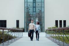 Dos amigos atractivos de los estudiantes que caminan en el camino del campus Imagenes de archivo