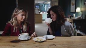 Dos amigos atractivos jovenes que hablan en un café, mujer en concepto del negocio