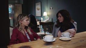 Dos amigos atractivos jovenes que hablan en un café, poder de la muchacha y escuchando