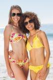 Dos amigos bonitos en los bikinis que llevan la presentación de las gafas de sol Foto de archivo libre de regalías