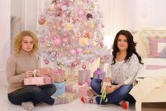 Dos amigos cercanos comparten emociones agradables y los regalos festivos, se sientan imágenes de archivo libres de regalías