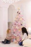 Dos amigos cercanos comparten emociones agradables y los regalos festivos, se sientan fotografía de archivo libre de regalías