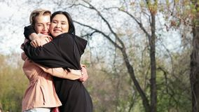 Dos amigos cercanos de diversas nacionalidades de las mujeres jovenes que se abrazan almacen de metraje de vídeo