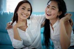 Dos amigos competitivos de las mujeres excitaron alegre feliz y la sonrisa foto de archivo