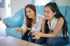Dos amigos competitivos de las mujeres que juegan los videojuegos y la ha emocionada imagen de archivo libre de regalías
