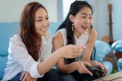 Dos amigos competitivos de las mujeres que juegan los videojuegos y la ha emocionada fotos de archivo libres de regalías