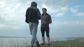 Dos amigos comunican en naturaleza almacen de metraje de vídeo