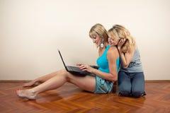 Dos amigos con la computadora portátil Fotografía de archivo libre de regalías