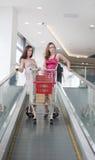 Dos amigos con las compras en la escalera móvil Imagen de archivo