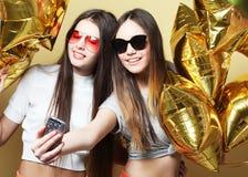 Dos amigos de adolescentes con los globos del oro hacen el selfie en un p Foto de archivo libre de regalías