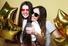 Dos amigos de adolescentes con los globos del oro hacen el selfie en un p Foto de archivo