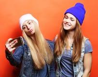 Dos amigos de adolescentes en equipo del inconformista hacen el selfie en un pho Imagenes de archivo