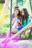 Dos amigos de chica joven que miran en el teléfono móvil Imagenes de archivo
